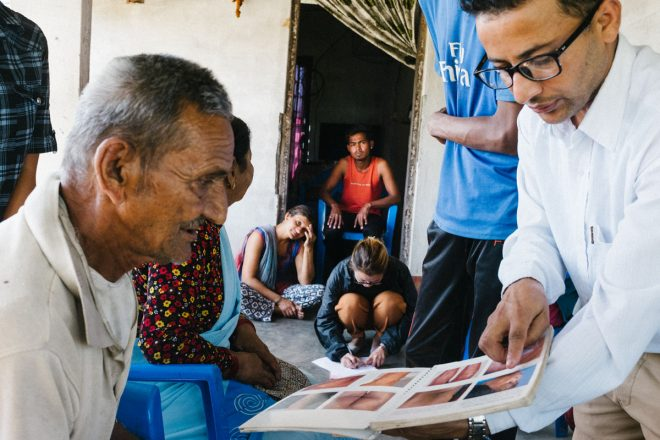 Leprosy doctor shows pictures of leprosy symptoms to contacts of leprosy patient
