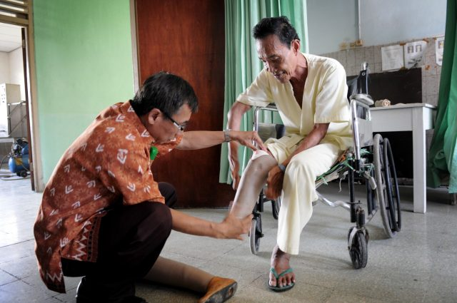 Person affected by leprosy receives a leg prosthese in order to be able to walk