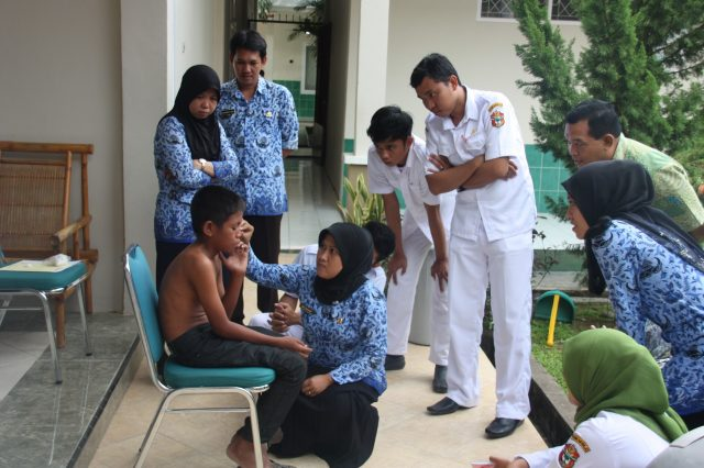 Leprosy medical staff checks Riduan from Indonesia on symptoms of leprosy
