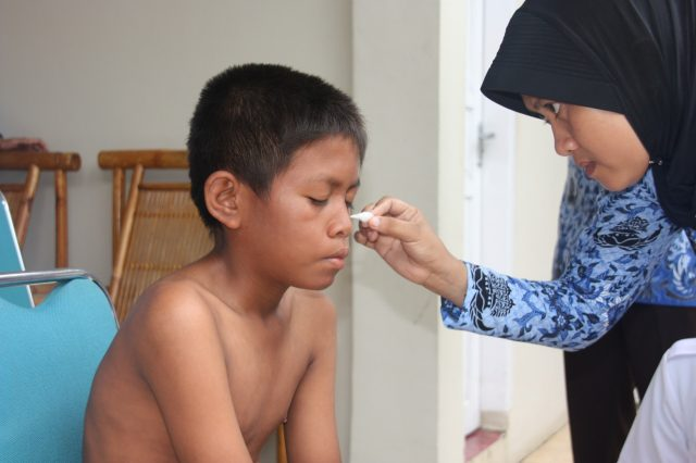 July, a health worker, treats Riduan, a person affected by leprosy