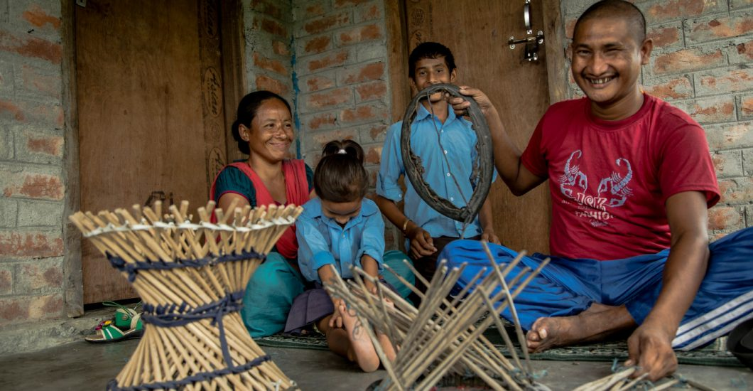 Person affected by leprosy Gobal making wooden stools to support his family