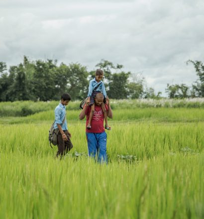 Person affected by leprosy Gobal with his children walking through the field